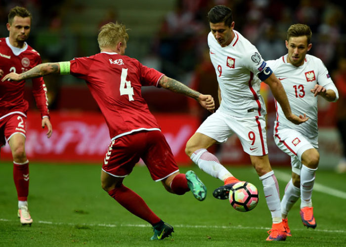 Dänemark in den roten Heimtrikots gegen die Polen mit Superstar Robert Lewandowski (R). Photo: AFP.