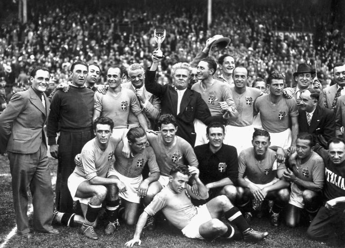 Italiens Nationalmannschaft gewinnt nach einem 4:2 Sieg gegen Ungarn die Fußball-Weltmeisterschaft 1938. (vorne von links : Amadeo Biavati (4th L), coach Vittorio Pozzo holding the trophy, Silvio Piola, Giovanni Ferrari, Gino Colaussi; erste Reihe von links : Ugo Locatelli, Giuseppe Meazza, Alfredo Foni, Pietro Serantoni, Aldo Olivieri, Pietro Rava and Michele Andreolo) / AFP PHOTO / STAFF