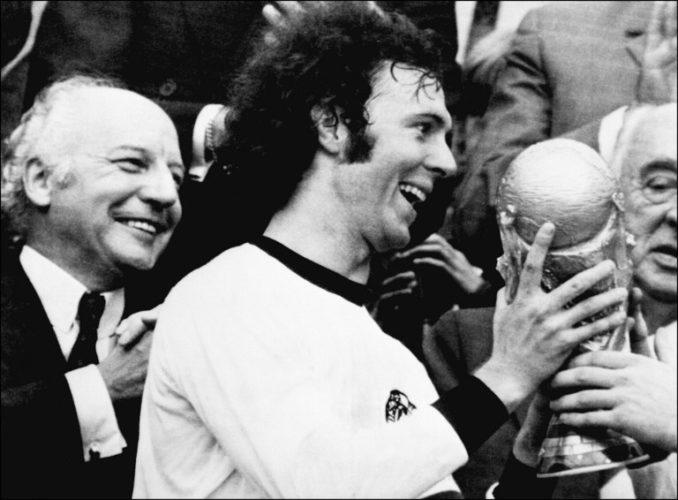 Kapitän Franz Beckenbauer erhält WM-Pokal nach dem 2:1 Sieg gegen Holland am 07. Juli 1974 . Deutschlands damaliger Bundespräsident Walter Scheel (L) applaudiert. (Foto AFP)