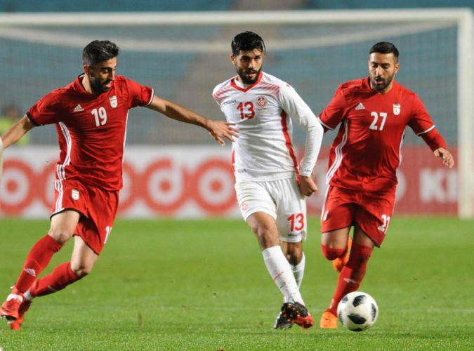 Tunisiens Mittelfeldspieler Ferjani Sassi (Mitte) im neuen weißen Heimtrikot 2018 und Iran's Kaveh Rezaei (L) und Saman Ghoddos (R) beim Testspiel am 23.März 2018. / AFP PHOTO / SALAH HABIBI